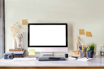 Stylish workspace with laptop computer, office supplies, houseplant and books at home or studio. Blank screen for graphics display montage.