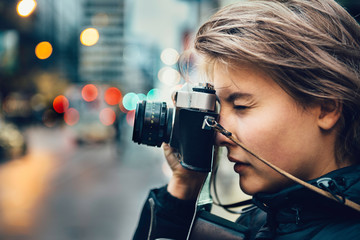 Beautiful tourist woman taking photo with vintage old camera in the city