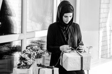 Young Woman Wearing Traditional Arabic dress with gift in hands.Black and white.
