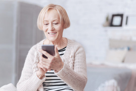 Positive minded senior lady looking at screen of her smartphone