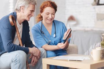 Friendly senior patient and nurse looking tablet computer