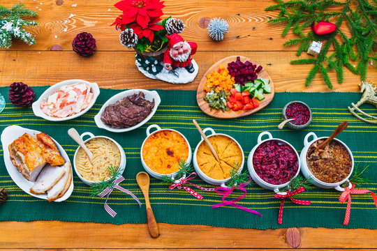 Finnish traditional Christmas table.potato, carrot, chestnut, red cabbage and liver casserole, ham, pulled beef, salmon, salad with carrot, beet,cucumber, apple,lingonberry puree.Top view.Rustic style