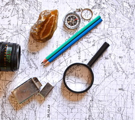 pencil, lens of vintage photo camera, mineral stone, magnifier, lighter and compass on old military topographical map