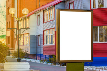 Billboard with blank white copy space for text message or content, mock up banner near the buildings lit by sunlight
