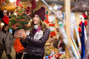 girl buying Xmas tree at festive fair in evening
