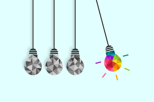 Newton's cradle pendulum with hanging light bulbs as idea and creativity concept. Colorful bulb among plain grey ones.