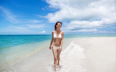 Sexy bikini body woman playful on paradise tropical beach having fun playing splashing water in freedom. Beautiful fit body girl on travel vacation
