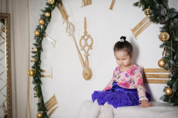 Beautiful little girl on a big New Year's clock. Child in Christmas decorations.