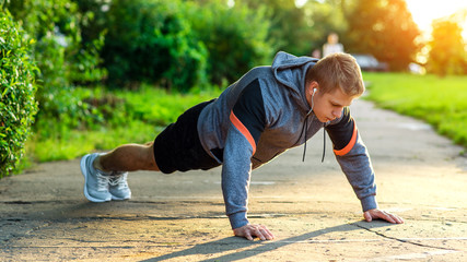 Male athlete exercising in the park. Portrait of a male guy doing push-ups. The concept of a healthy lifestyle. Strength and motivation