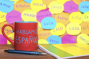 Study Spanish concept, a mug with written words Speak Spanish, notebook, pen and notes with common spanish words.