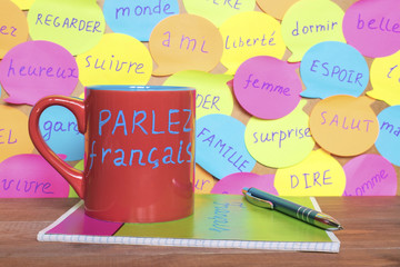 Study French concept, a mug with written words Speak French, notebook, pen and notes with common french words.