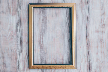 Gold frame on a wooden background.Rustic style.