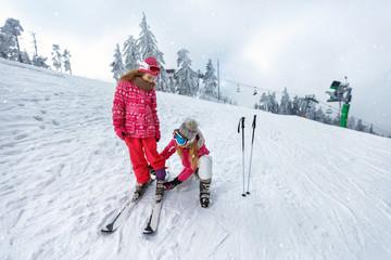 Skiing, winter fun-Mother preparing for skiing daughter