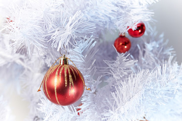 Red and Golden Christams Balls hanging on a white christmas tree