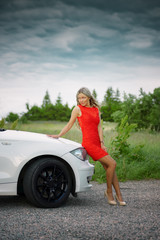 Young beautiful woman in red dress near white car