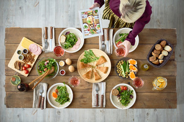 Above view of dinner table with delicious food and young woman taking photos of it