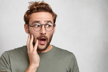 Stunned shocked bearded man with jaw dropped, listens to unbelievable story, can`t trust in it. Male looks with full disbelief aside, isolated over white background. People, reaction concept