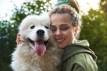 young woman in green coat and multicolored dreadlocks with his white Samoyed dog posing for a picture with closed eyes in autumn Park