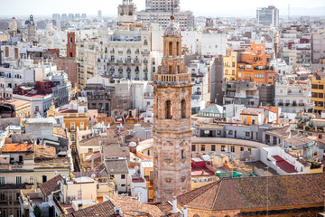 Top cityscape view on the old residential buildings with church tower in Valencia city during the sunny day in Spain