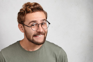 Cheerful male grins at camera, bits lower lip, being glad to achieve goals. Funny bearded young man with trendy hairdo, wears glasses, smiles pleasantly, expresses positive emotions and feelings