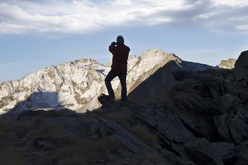L'escursionista fotografa la montagna illuminata dal sole.