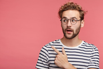Shocked bearded young man with trendy hairdo and mustache points at copy space as poses against pink background, advertises something or being surprised to see high prices. It`s unbelievable!