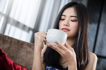 beautiful asian woman in white shirt relax and clam with hot drink with happiness moment with white curtain background