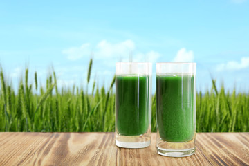 Shots of juice and wheat grass field on background
