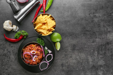 Bowls with chili con carne and nachos on grey background