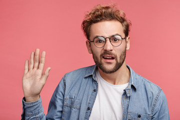 Indignant man wears jean shirt, waves with palm as tries to remind about himself. Active male student being puzzled, wants to give answer on question. Confused adult waves with hand in pink studio