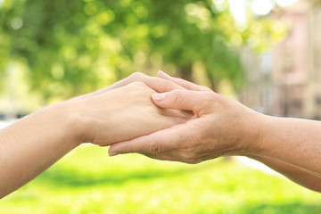 Mother and daughter holding hands together outdoors, closeup