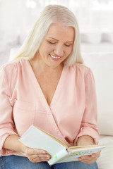 Attractive mature woman reading book at home