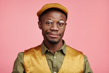 Headshot of young African American stylish hipster guy wears cap, round glasses, curves lips in bewilderment, recieves invitation on birthday party, doesn`t know what present to buy for friend