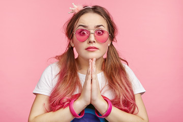 Pin up girl pleads. keeps palms together, asks for something. Couquette young fashionable female model whose favourite colour is pink, wears many accessories, has bated breath, waits for something