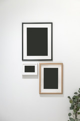 group of photo frames hanging against the white wall