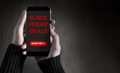 Black Friday Promotional Concept, Female holding Smart Phone with Advertising on the Screen for Online Shopping