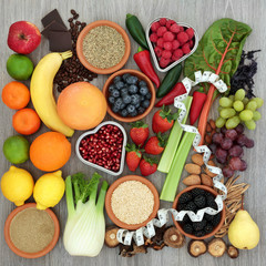 Diet health food concept with tape measure, vegetables, fruit, coffee, grains, nuts, chocolate and herbs with gymnema sylvestre and tribulus terrestris used as an appetite suppressant.