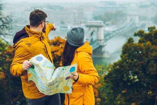 couple holding map in hands in autumn day