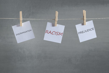 Racism, prejudice and discrimination words on notes hanging on a clothesline. Social issues concept