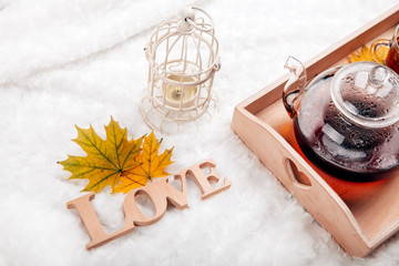 autumn home scene, Scandinavian style. A warm knitted sweater, candles, a cup of warm tea and other decor on a tray in bed.