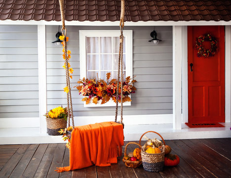 interior of an autumn patio. swing is adorned with autumn leaves and orange knitted plaid. Basket with pumpkins and autumn vegetables. The window is decorated with autumn decor.