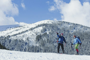 Winter Trekking in the mountains. Two men make an ascent to the top.
