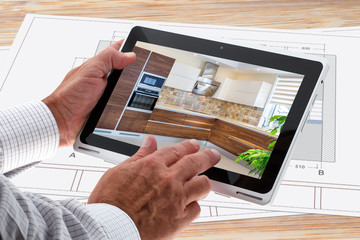 Man Hands Holding Tablet. Photo Of Classic Kitchen Interior Design On Screen. Drawing In Background. Home Interior Design Software Programs. Project management.