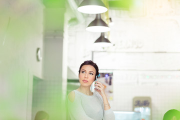 Attractive woman speaking by cellphone in cafe