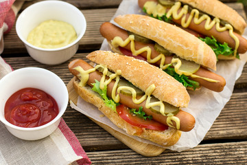 Hot dog in a bun with mustard and vegetables
