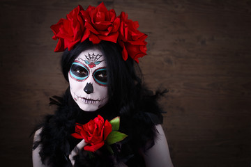 Day of the dead. Halloween. Young woman in day of the dead mask skull face art and rose. Dark background.