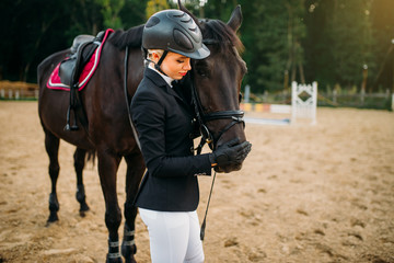Young woman in helmet hugs horse, horseback riding