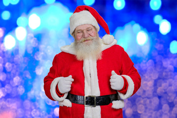 Santa Claus on blue shiny background. Authentic Santa Claus with real beard and eyeglasses standing on blurred background. Brightful photo of realistic Santa Claus.