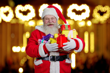 Santa Claus holding boxes with gifts. Smiling Santa Claus holding a pile of gift boxes against light design shimmering on dark.