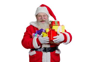 Joyful Santa Claus holding Christmas presents. Cheerful Santa Claus holding pile with gift boxes, isolated on white background.